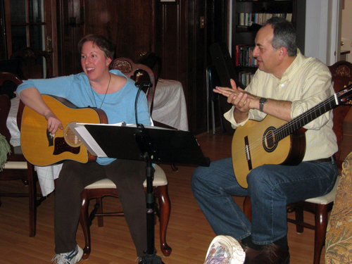 Photo of two people playing guitars and singing.
