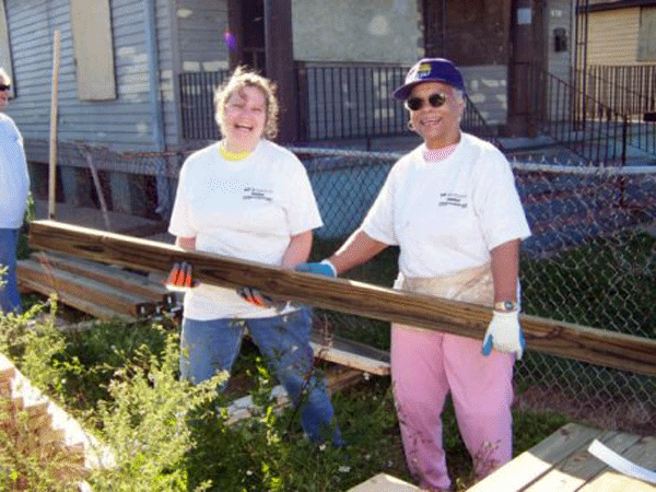 Photo of Betty Mongomery working with Habitat for Humanity carrying a long board