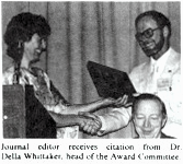 Photo of Dr. Della A. Whitaker handing award to editor